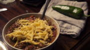 Finished chili in a bowl with shredded cheese and a raw jalapeno on the side